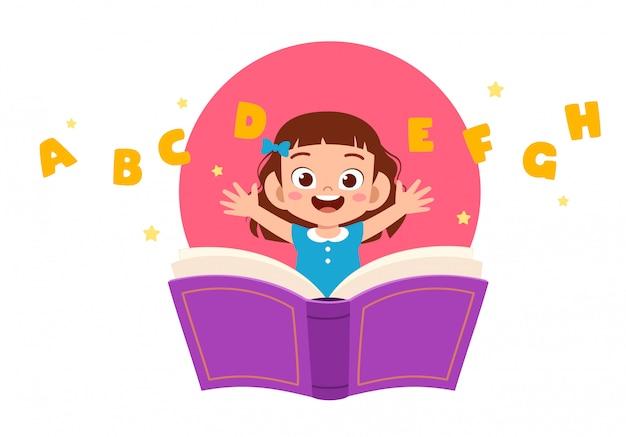 Ragazza sveglia felice del bambino con il libro e la lettera
