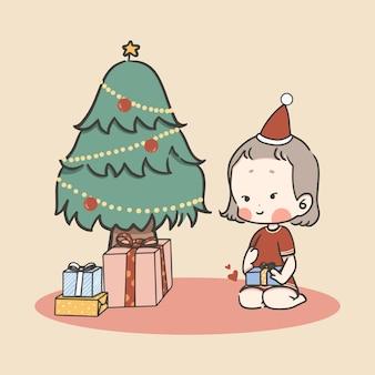 Ragazza sveglia felice del piccolo bambino soddisfatta del contenitore di regalo di natale con l'albero di natale