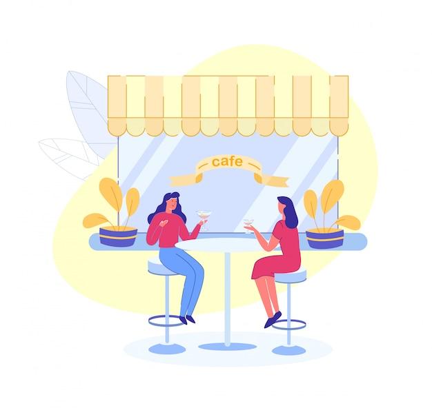 Ragazze che bevono alcolici e chiacchierano in street cafe