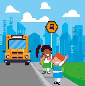 Ragazze dello studente alla fermata dell'autobus con la città del fondo