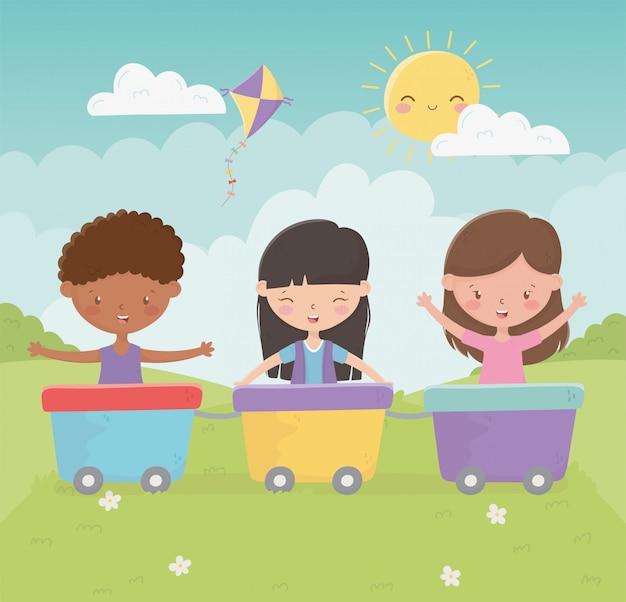 Ragazze e ragazzo del giorno dei bambini felici che giocano con i vagoni