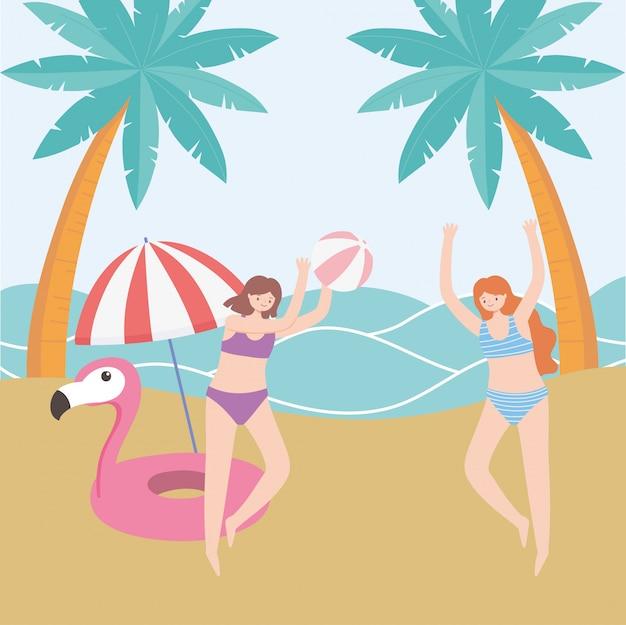 Ragazze turistiche di vacanza di ora legale che giocano con la palla in spiaggia