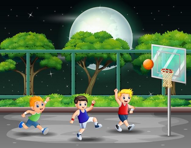 Ragazzi felici giocando a basket a corte nella notte