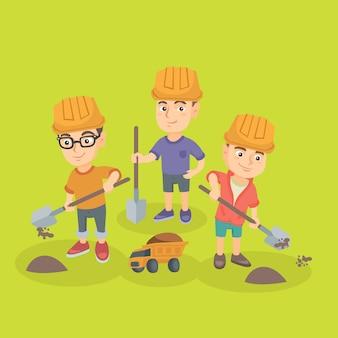 Ragazzini che giocano con sabbia, vanga e camion giocattolo