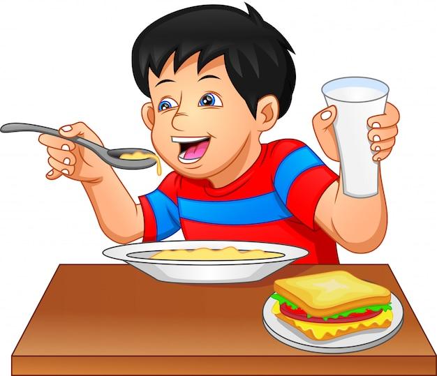 Ragazzino che mangia porridge e sandwich