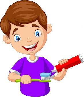 Ragazzino sveglio che schiaccia dentifricio in pasta su uno spazzolino da denti
