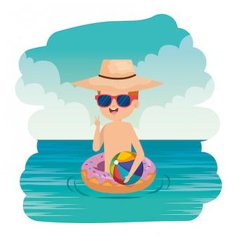 Ragazzino sveglio con ciambella galleggiante e pallone da spiaggia sul mare
