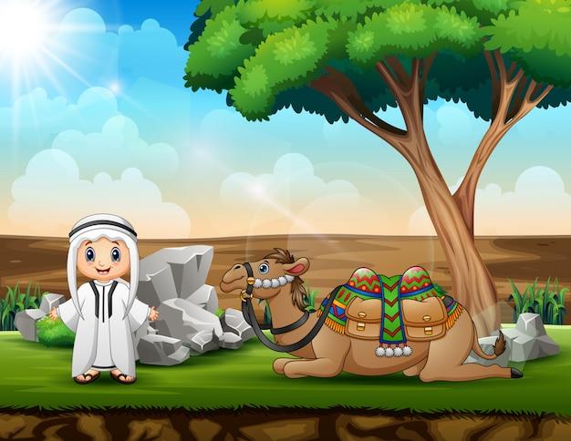 Ragazzo arabo e un cammello che riposa sotto l'albero