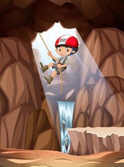 Ragazzo che si cala in corda doppia nella caverna