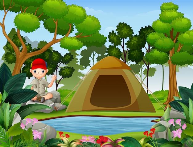 Ragazzo che si siede sopra la roccia vicino ad una tenda