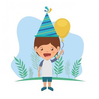 Ragazzo con cappello da festa e palloncino ad elio nella celebrazione del compleanno