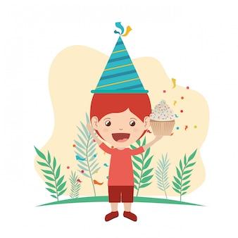 Ragazzo con il cappello e la torta del partito nella celebrazione di compleanno