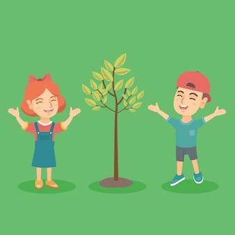 Ragazzo e ragazza caucasici felici che saltano vicino all'albero