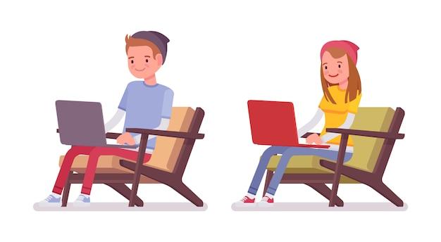 Ragazzo e ragazza dell'adolescente che si siedono con il computer portatile
