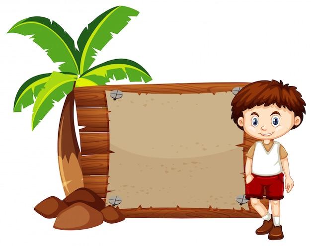 Ragazzo e segno felici sul bordo di legno