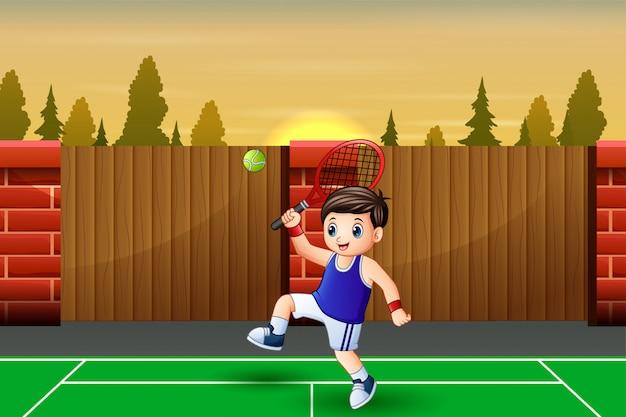Ragazzo felice che gioca a tennis alle corti