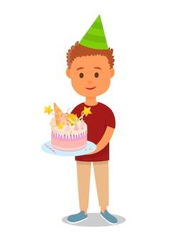 Ragazzo in cappello compleanno tenendo la torta con i dolci.