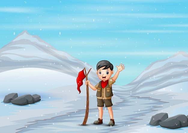 Ragazzo scout che cammina attraverso la strada nevosa nella stagione invernale