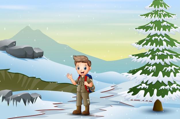 Ragazzo scout con lo zaino che cammina sulla neve