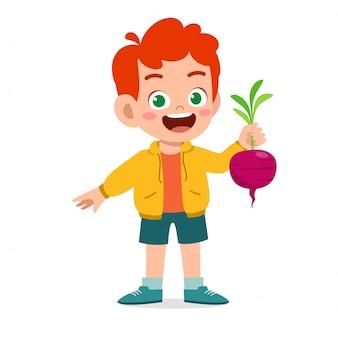 Ragazzo sveglio felice del bambino che tiene verdura fresca