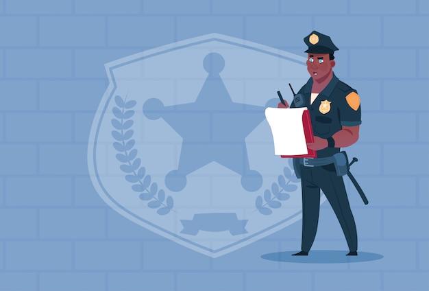 Rapporto di scrittura del poliziotto afroamericano che indossa la guardia di uniforme uniforme sopra il fondo del mattone