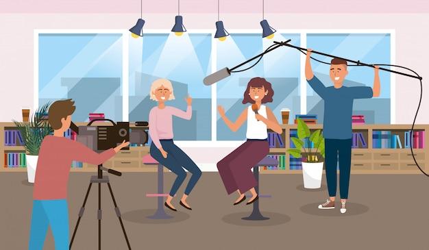 Reporter donne in studio con uomini fotocamera e attrezzature videocamera