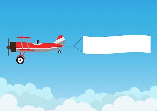 Retro volo dell'aeroplano con la bandiera di pubblicità su cielo blu