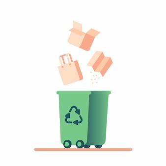 Riciclaggio dei rifiuti di carta. il cartone cade in un cestino verde con un simbolo di riciclo.