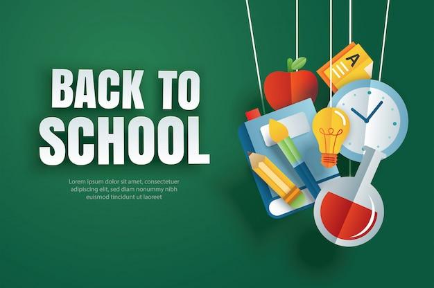 Ritorno a scuola con oggetti di educazione appesi su carta verde.
