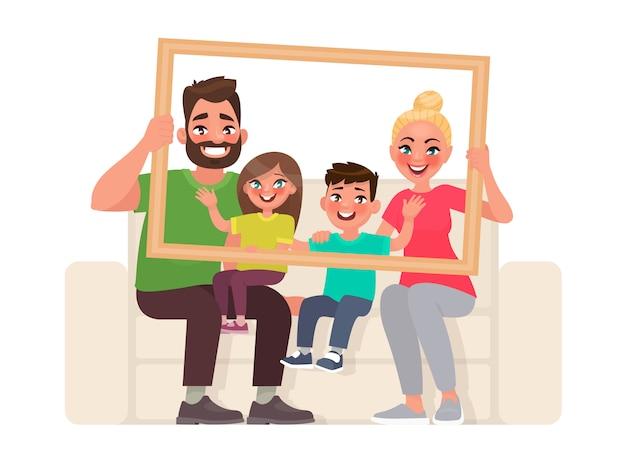 Ritratto di famiglia. papà, mamma, figlio e figlia seduti sul divano, con in mano una cornice
