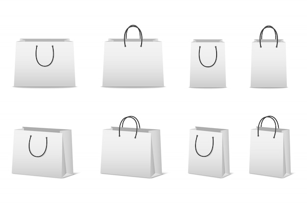 Sacchetti della spesa della carta in bianco messi isolati su bianco
