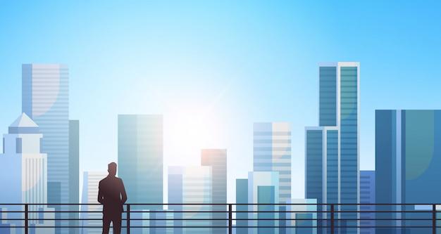 Sagoma di uomo d'affari in piedi sopra la città moderna