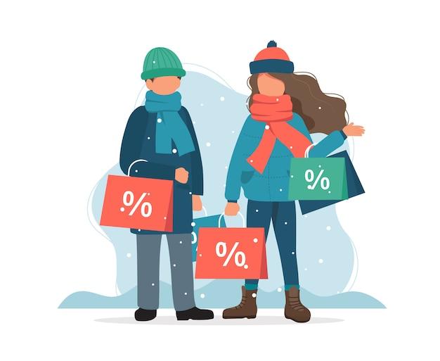 Saldi invernali, uomo e donna con borse della spesa in inverno.