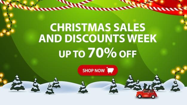 Saldi natalizi e settimana scontata, fino al 70% di sconto, banner sconto orizzontale verde con pulsante, ghirlanda di cornici, foresta invernale di pini e albero di natale rosso con auto d'epoca.