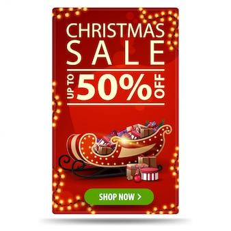 Saldi natalizi, fino al 50% di sconto, banner rosso verticale con ghirlande, bottone e slitta di babbo natale con regali