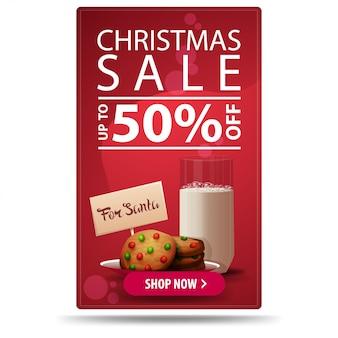 Saldi natalizi, fino al 50% di sconto, banner sconto verticale rosso con pulsante e biscotti con un bicchiere di latte per babbo natale
