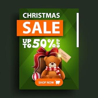 Saldi natalizi, fino al 50% di sconto, banner verde verticale con bottone e presente con orsacchiotto
