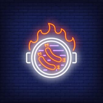 Salsicce sulla griglia del barbecue con l'insegna al neon della fiamma del fuoco