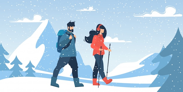Scalatori delle coppie della montagna che camminano via la forte nevicata