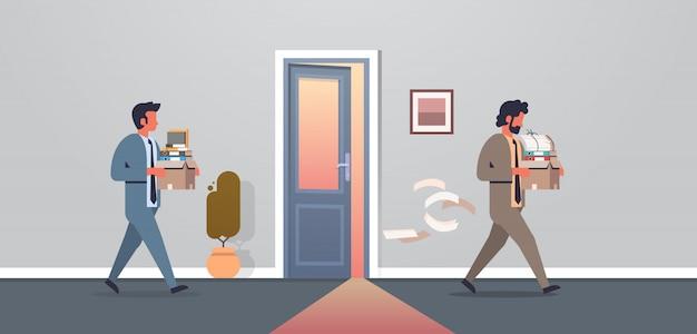 Scatola di trasporto dell'uomo di affari con le cose la porta dell'ufficio del nuovo posto di lavoro ha respinto frustrato