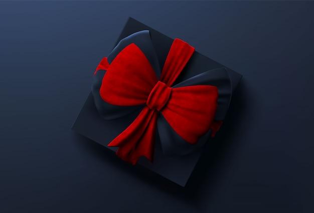 Scatola regalo nera con nastro rosso e fiocco, vista dall'alto.