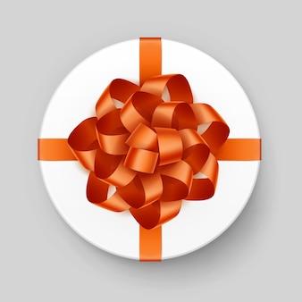 Scatola regalo rotonda bianca con fiocco arancione brillante e vista dall'alto del nastro vicino isolato su sfondo