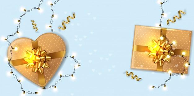 Scatole regalo in oro con ghirlanda di luci