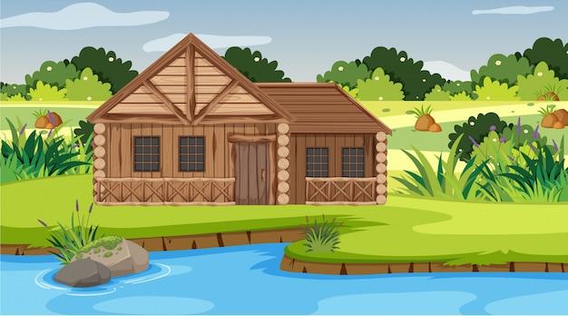 Scena con casa di legno nel campo