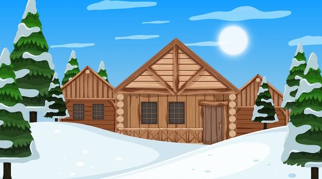 Scena con cottage in legno e pini nel campo di neve