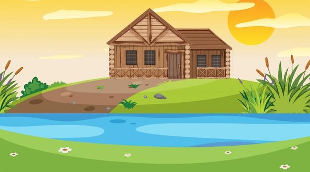 Scena con cottage in legno nel campo al tramonto