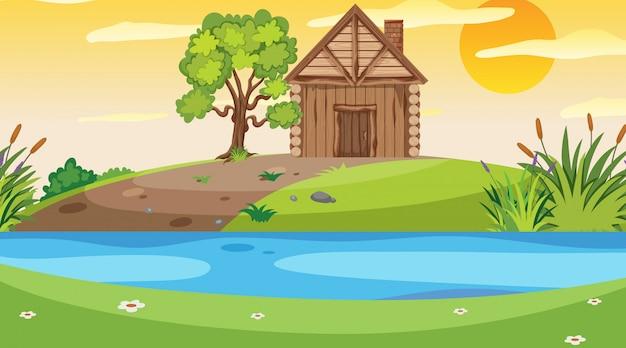 Scena con cottage in legno nel campo sul fiume