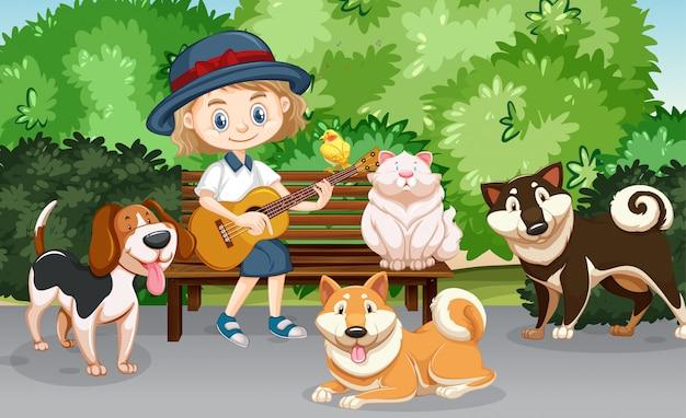Scena con ragazza carina suonare la chitarra e molti animali domestici nel parco