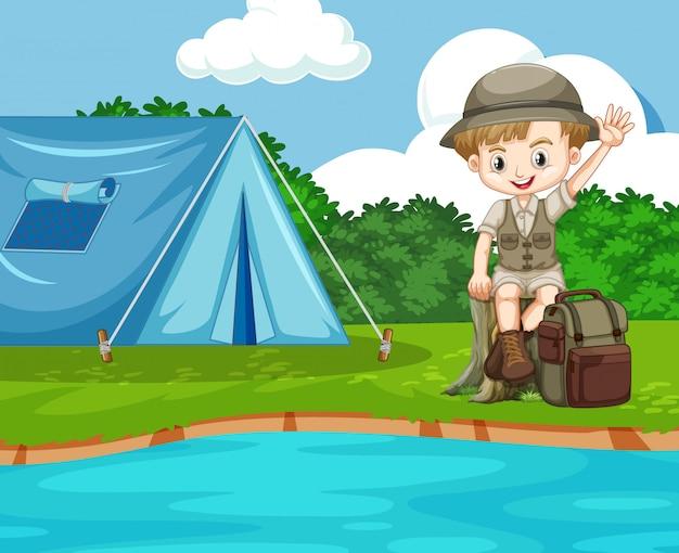 Scena con ragazzo carino campeggio in riva al fiume