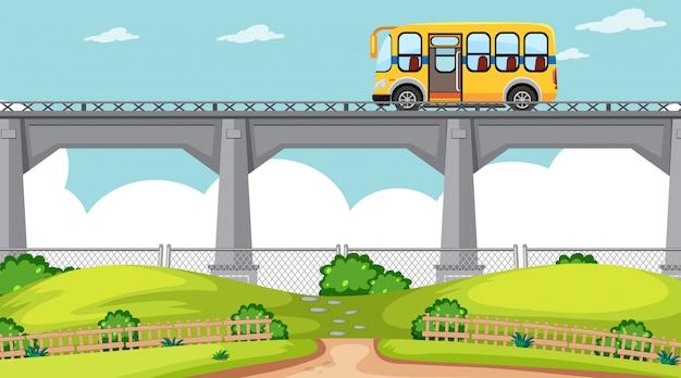 Scena di ambiente naturale con autobus vicino al ponte